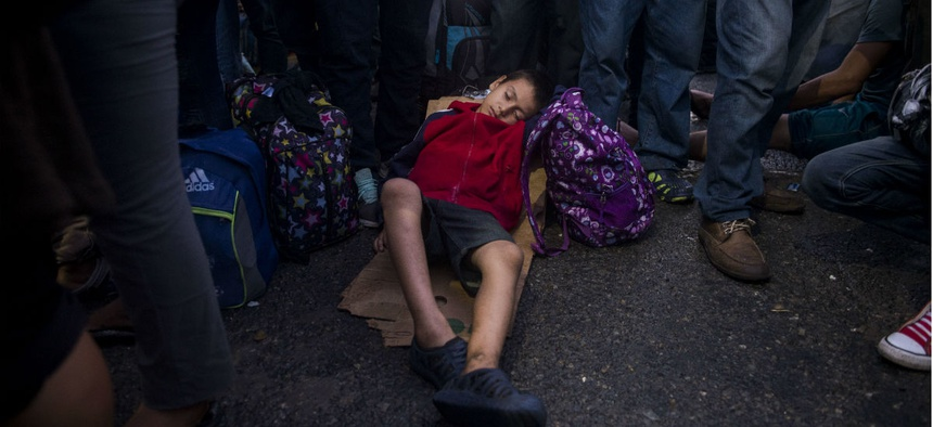 "A child in the ""caravan"" of largely Guatemalan, Honduran and El Salvadoran citizens sleeps on a bridge connecting Guatemala and Mexico."