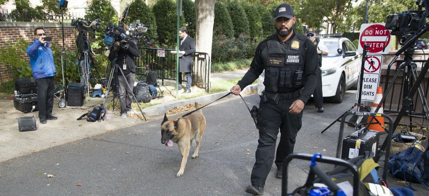 A Secret Service officer and his dog search for bombs at a checkpoint near former President Obama's home in Washington on Wednesday. Obama was one of the officials targeted with the explosive devices.
