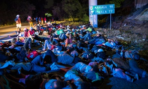 Early in the morning migrants sleep next to the highway, as a thousands-strong caravan of Central American migrants slowly makes its way toward the U.S. border, between Pijijiapan and Arriaga, Mexico on Friday.