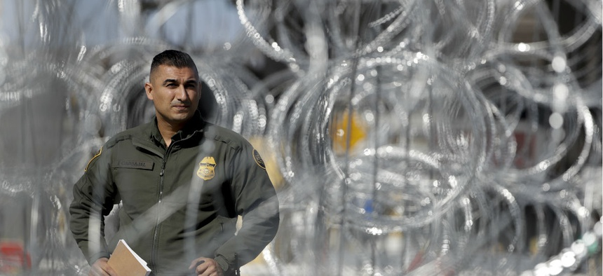 A U.S. Border Patrol agent looks through concertina wire during a tour of the San Ysidro port of entry on Nov. 16, 2018, in San Diego.