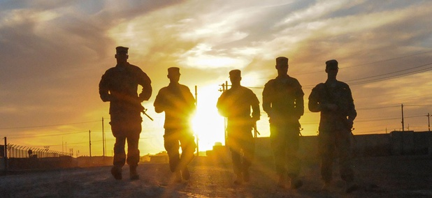 A group of U.S. Soldiers walks along the road at sunset in Taji, Iraq, in 2016.