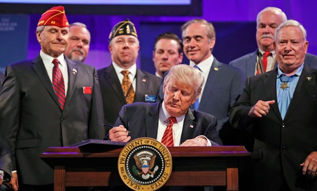 President Donald Trump prepares to sign the Veterans Appeals Improvement and Modernization Act in 2017.