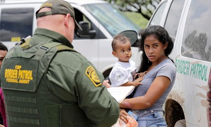 A mother migrating from Honduras holds her 1-year-old child as surrendering to U.S. Border Patrol agents after illegally crossing the border near McAllen, Texas in June.