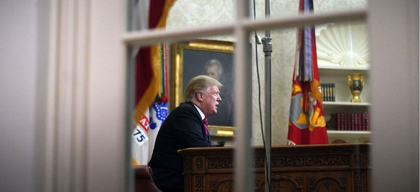 As seen from a window outside the Oval Office, President Donald Trump gives a prime-time address about border security on Tuesday evening.