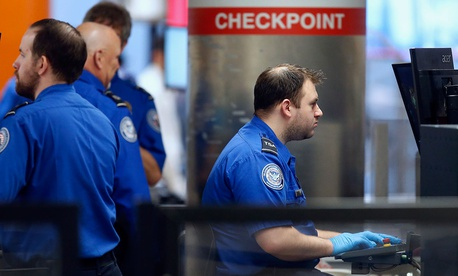 Transportation Security Administration officers work at a checkpoint at Logan International Airport in Boston on Saturday.