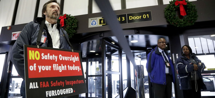 FAA employee Michael Jessie, who is currently working without pay as an aviation safety inspector for New York international field office overseeing foreign air carriers, holds a sign at Newark Liberty International Airport Jan. 8.