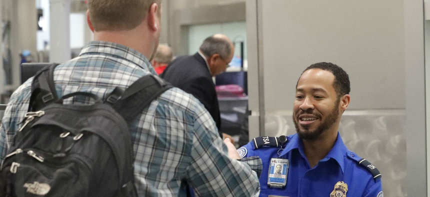 A TSA employee screens a passenger at Hartsfield-Jackson Atlanta International Airport in early January. The airport is one of several that have had to make adjustments due to unscheduled absences.