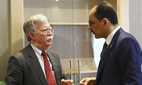 U.S. National Security Adviser John Bolton, left, and his Turkish counterpart and senior adviser to President Recep Tayyip Erdogan, Ibrahim Kalin, right, talk at the Presidential Palace in Ankara, Tur