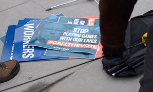 Signs from a rally protesting the shutdown sit on the ground on Thursday at Nationals Park in D.C.