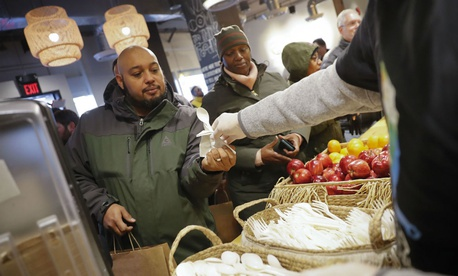 A volunteer hands out food at Chef Jose Andres' World Central Kitchen pop-up site in D.C. for federal employees affected by the shutdown.