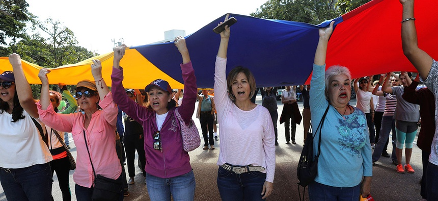 Members of the opposition hold up a Venezuelan flag and sing their national anthem before handing out explainers to soldiers and police about an amnesty law, near Ft. Tiuna military base in Caracas on Sunday.