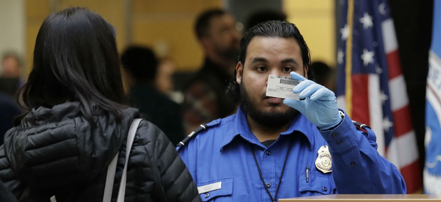 A TSA worker checks an identification card during the shutdown at Seattle-Tacoma International Airport. TSA staff were among the federal workers compelled to work without pay during the shutdown.