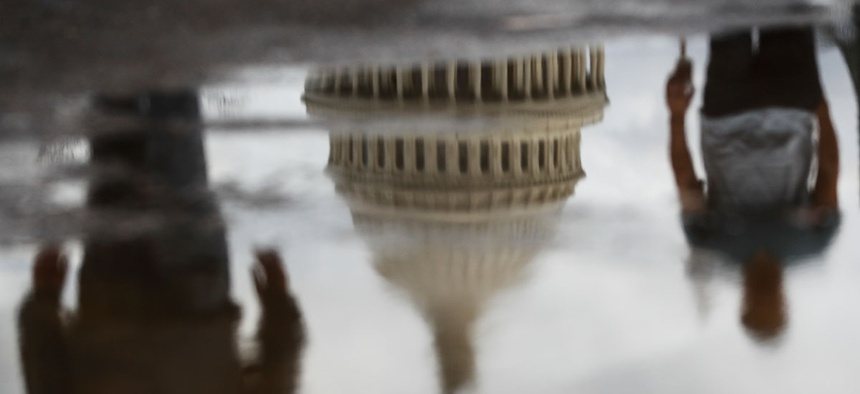 The Capitol Building and pedestrians are reflected in a puddle in 2017.