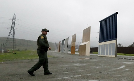 A Border Patrol agent approaches border wall prototypes in San Diego, Calif., earlier this month.