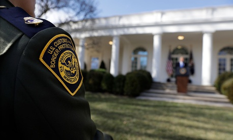 A CBP agent watches as Trump speaks on Friday.