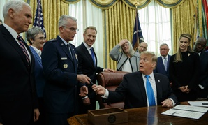 "President Donald Trump hands a pen to Air Force Gen. Paul Selva after signing ""Space Policy Directive 4"" in the Oval Office on Tuesday."
