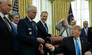 "President Donald Trump hands a pen to Air Force Gen. Paul Selva after signing ""Space Policy Directive 4"" in the Oval Office of the White House Feb. 19."