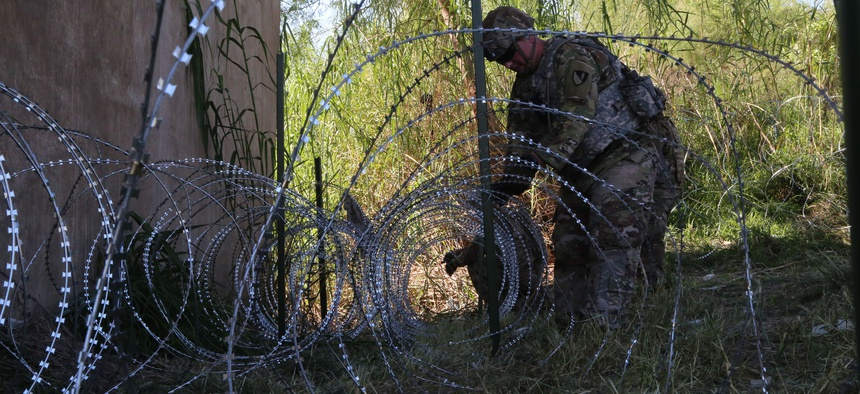 Soldiers deploy concertina wire in a location along the Southwest border of the United States near Hidalgo, Texas in November.