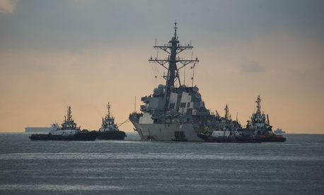 The USS John S. McCain is towed away from the pier at Changi Naval Base in 2017.