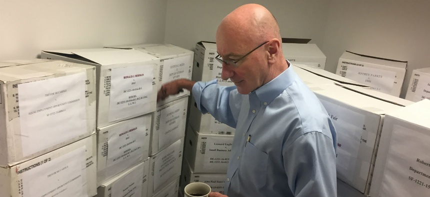 Mark Robbins, the last remaining member on MSPB's central panel, points out boxes full of cases. Thursday is Robbins's last day.
