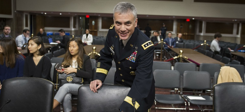 Army Lieutenant General Paul Nakasone arrives at the witness table to appear before the Senate Armed Services Committee to discuss his qualifications as nominee to be National Security Agency Director and U.S. Cyber Command Commander, during a hearing.