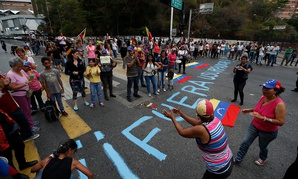 """People stand around the message """"Get out usurper!"""" as they protest the government of Venezuela's President Nicolas Maduro in Caracas on Tuesday"""