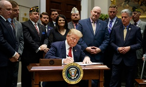 "President Donald Trump signs an executive order on a ""National Roadmap to Empower Veterans and End Veteran Suicide"" at the White House on March 5."