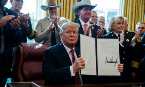 President Donald Trump signs the first veto of his presidency in the Oval Office of the White House on Friday.