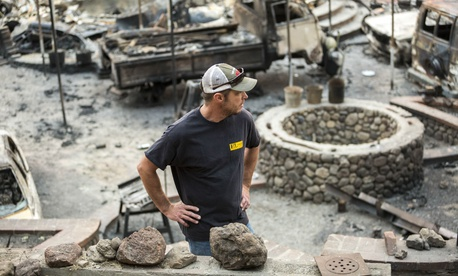 A man stands in the ruins of his burned home in Glen Ellen, California, in October 2017 after wildfires devastated the region.