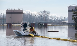 Contracted employees of the Environmental Restoration, LLC company deploy a spill containment boom around the Offutt Air Force Base fuel storage area as a precautionary measure March 18, 2019 following flooding of the southeast portion of the base.