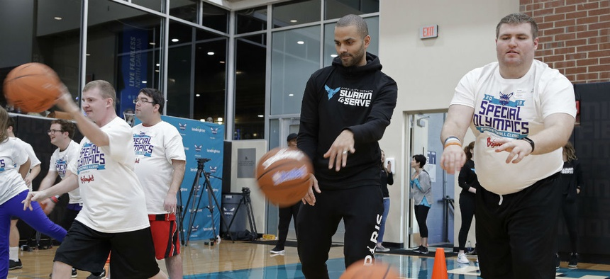 The Charlotte Hornets' Tony Parker, second from right, practices passing with athletes during a basketball clinic for Special Olympics athletes in January.