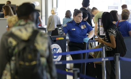 A TSA employee looks over passengers at a security checkpoint at LaGuardia Airport in New York.