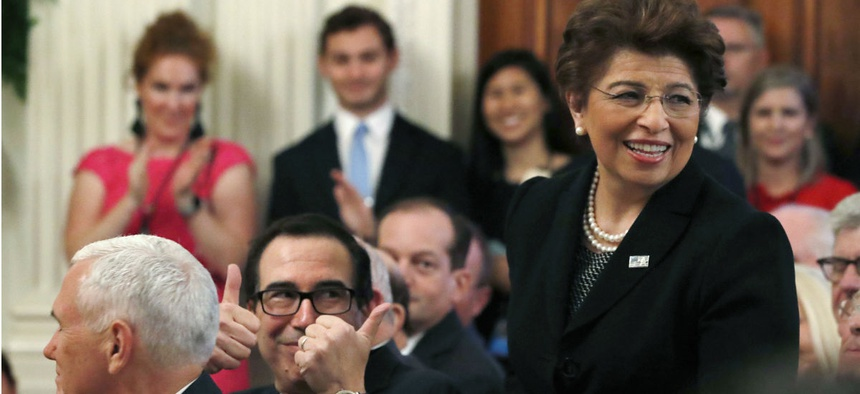 Treasury Secretary Steve Mnuchin, left, gives two thumbs up for U.S. Treasurer Jovita Carranza, right, as she is acknowledged by President Donald Trump at an event about taxes in June 2018.
