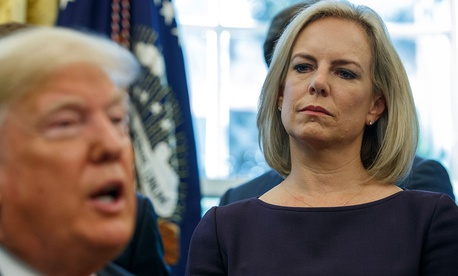 """Secretary of Homeland Security Kirstjen Nielsen looks on as President Donald Trump speaks during a signing ceremony of the """"Cybersecurity and Infrastructure Security Agency Act,"""" in the Oval Office in 2018."""