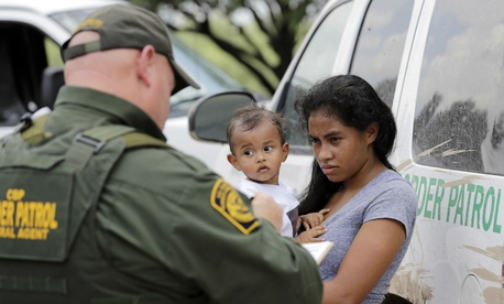 A mother migrating from Honduras holds her 1-year-old child as surrendering to U.S. Border Patrol agents after illegally crossing the border June 25, 2018, near McAllen, Texas.