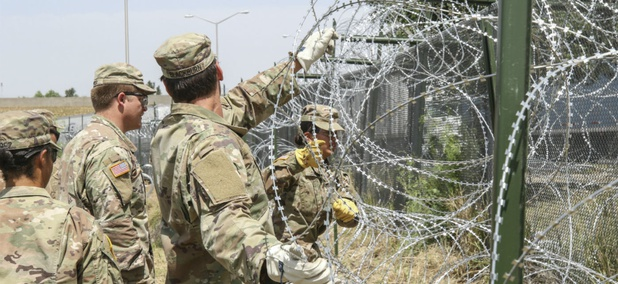Soldiers from the 161st Engineer Support Company (Airborne) stretch out concertina wire to secure to the existing border fence near the World Trade International Bridge in Laredo, Texas