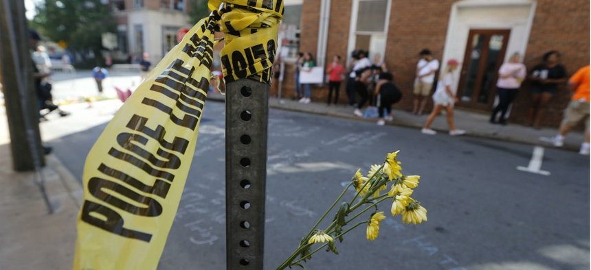 Police tape and flowers mark the site where a car plowed into a crowd of people protesting a white nationalist rally in August 2017 in Charlottesville, Va.