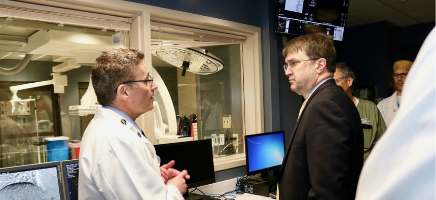 Veterans Affairs Secretary Robert Wilkie, right, tours a medical facility in August 2018.