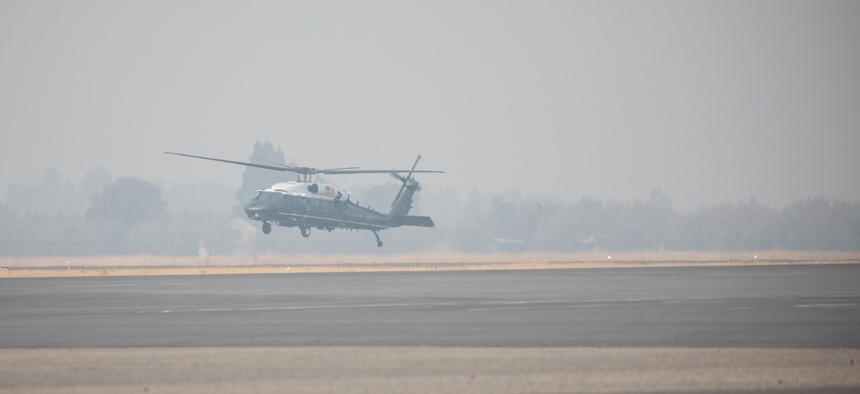 Marine One with President Donald J. Trump aboard departs in a smoky haze from Beale Air Force Base, Calif. after the wildfires in November.