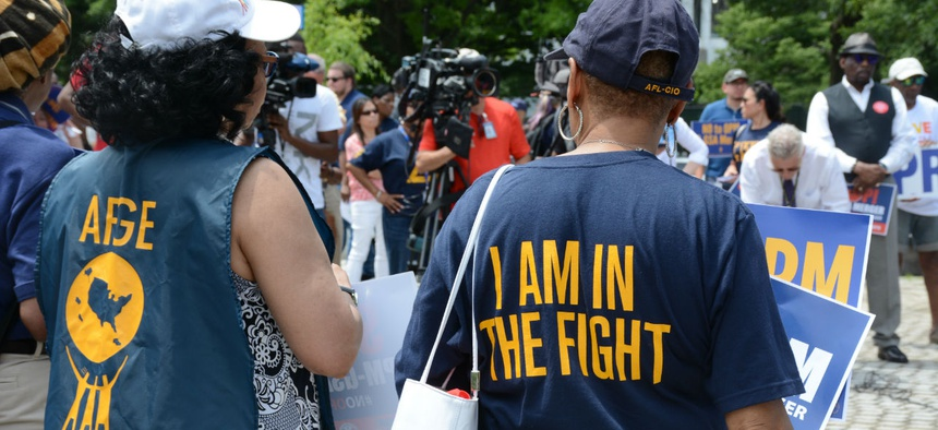 AFGE members in June protest a proposed merger of OPM and GSA.  Unions say the dues proposal would make it harder for them to represent federal workers.