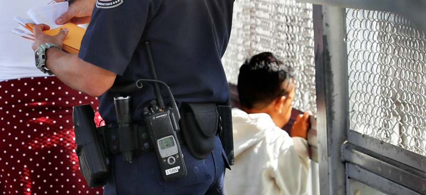A United States Customs and Border Protection Officer checks the documents of migrants, before being taken to apply for asylum in the United States, on the International Bridge 1 in Nuevo Laredo, Mexico.