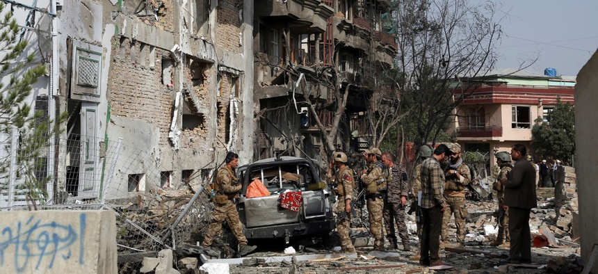 Afghan security forces inspect the aftermath of Sunday's attack in Kabul on Monday.