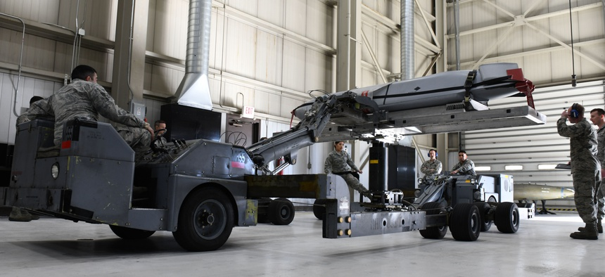 Load crew members from the 28th Munitions Squadron use a munitions lift truck or 'jammer', to load an inert AGM-158 Joint Air-to-Surface Standoff Missile into a simulated B-1 bomber.