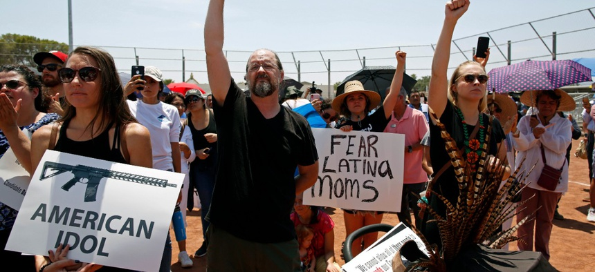 Demonstrators hold signs and raises their fists to protest the visit of President Donald Trump on Wednesday in El Paso.