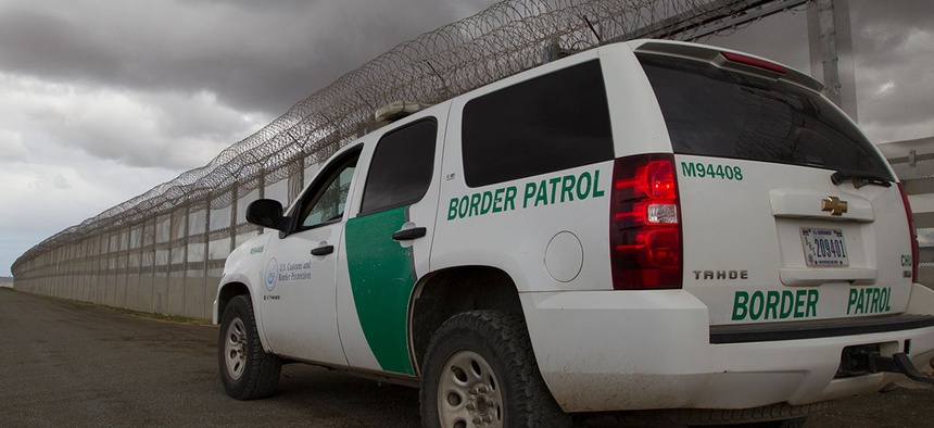 A Border Patrol vehicle sits along the border barrier separating San Diego and Tijuana in 2016.