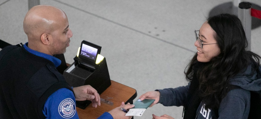 A Transportation Security Administration agent reviews a passenger's ID and ticket at a security checkpoint at New York's John F. Kennedy International Airport.