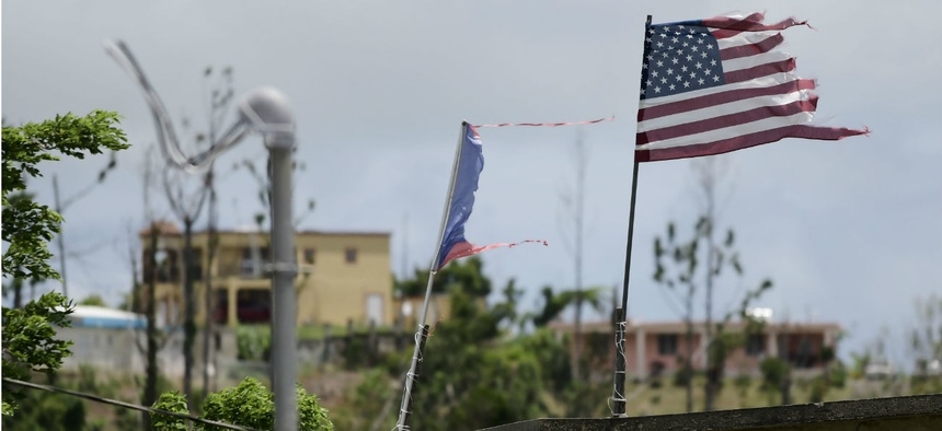 In this May 2018 photo, deteriorated U.S. and Puerto Rico flags fly in an area that remained without power eight months after Hurricane Maria devastated the island.