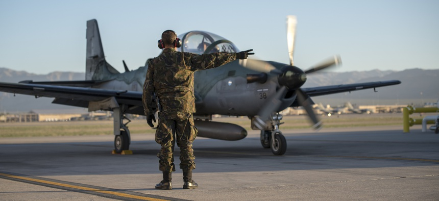 1st Sgt. DeBarros, a crew chief with the Brazilian Air Force, goes over pre-flight checks during Green Flag-West 19-8 at Nellis Air Force Base, Las Vegas, Nevada, June 8, 2019.