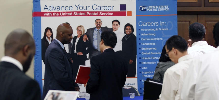 In this Aug. 4, 2011 photo, job seekers line up at the U.S. Postal Service booth during a career job fair in Arlington, Va.