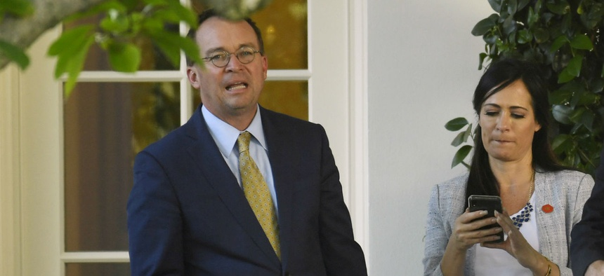 Acting White House Chief of Staff Mick Mulvaney looks on as President Trump speaks to reporters in August.